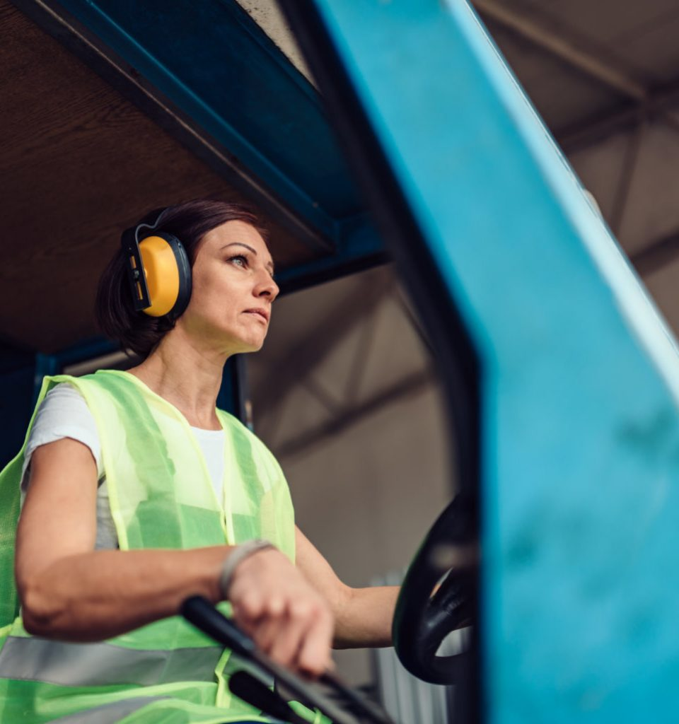 Woman forklift operator driving vehicle at industrial factory