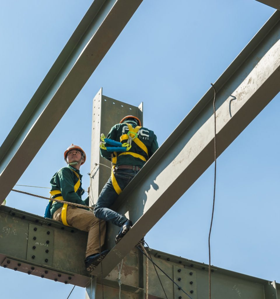 Ho Chi Minh City, Vietnam - September 18, 2014: Builder workers in safety protective equipment assemble metal construction frame with spanner tools in Ho chi Minh City on Sep 18, 2014