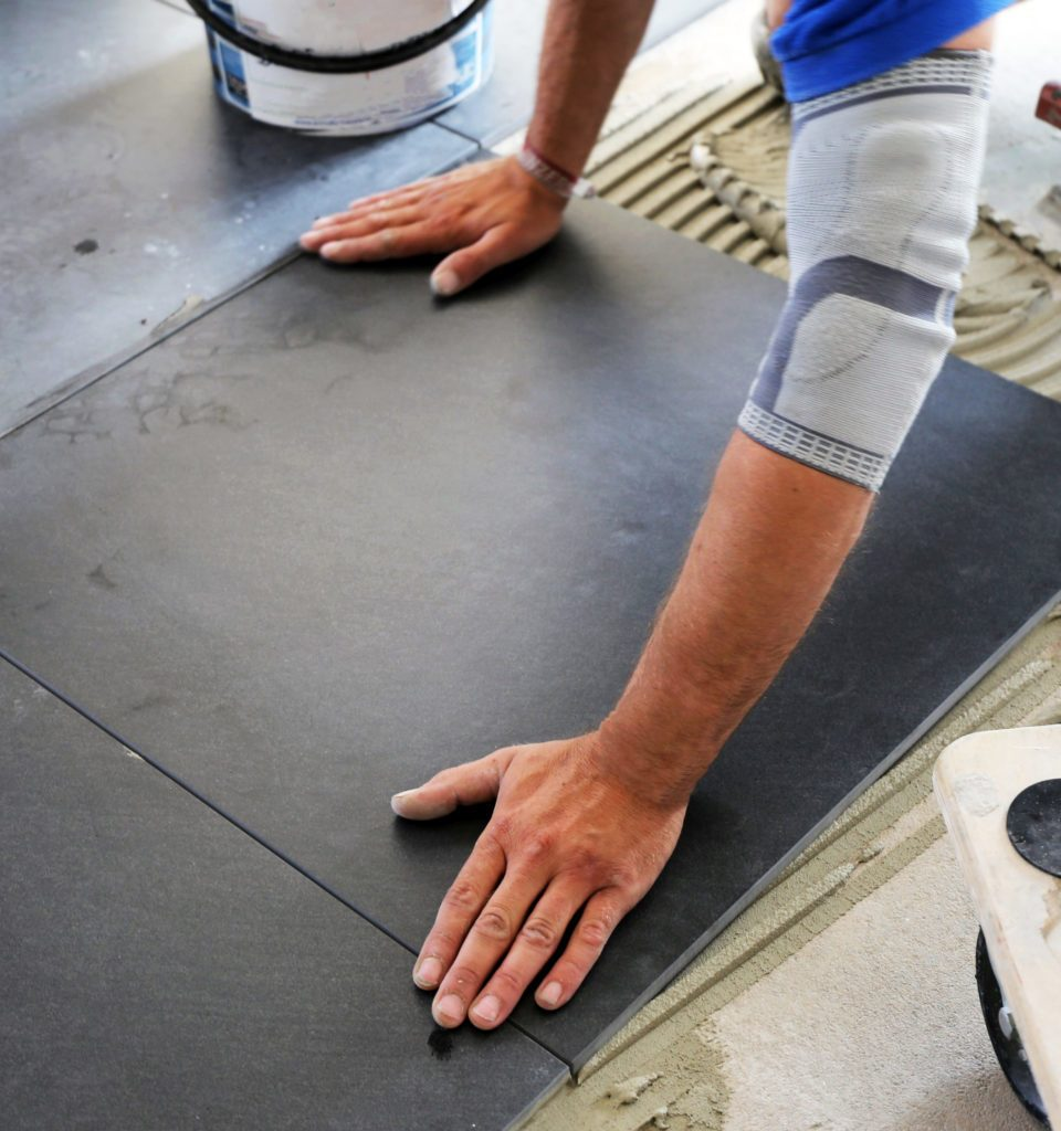 Worker laying floor tiles, close up